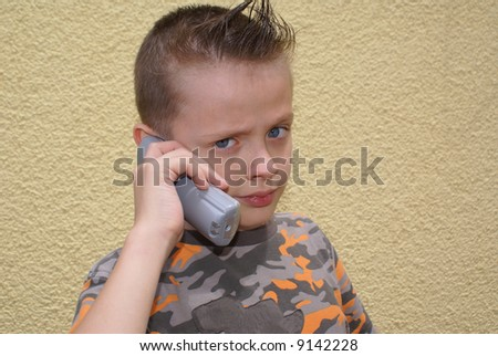 Twelve boy with a fashionable haircut and a telephone in his hand.