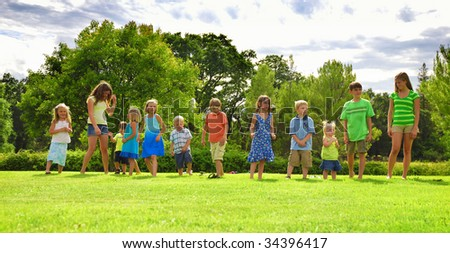 Twelve kids lined up on grass for a race