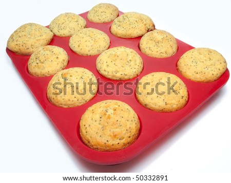 twelve lemon poppy seed muffins freshly baked in red silicone nonstick baking tray on white background