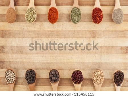 twelve spices on spoons on cutting board