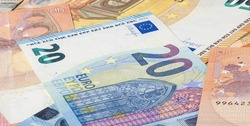 Twenty Euro bill in between a big pile of euro banknotes.  Bunch of money of the European Union. Currency of the united Europe. Cash balance of the European Central Bank or ECB. 20 Euro cash on table
