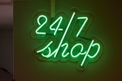 Twenty-four hours shop neon sign glowing on a wall
