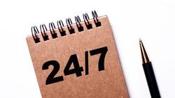 Twenty four on seven written in black on a brown notebook near a pen on a white background