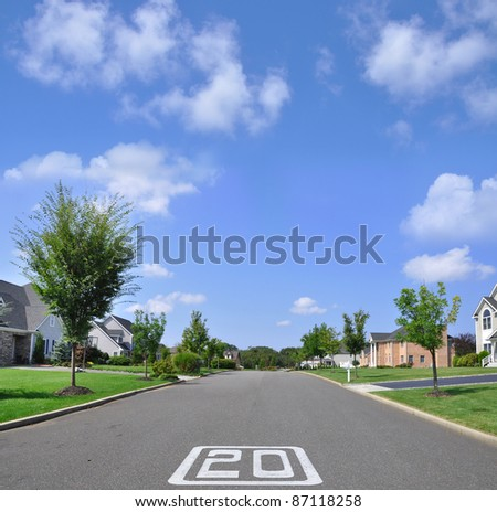 Twenty Mile an Hour traffic sign on Empty Street of Suburban Residential Neighborhood under blue sky with clouds - stock photo