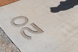 Twenty number stamped on concrete floor and human shadow on floor. Abstract scene