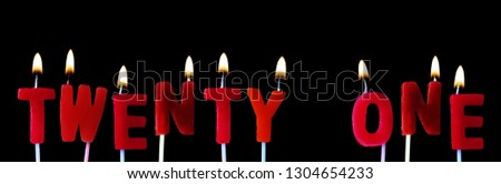 Twenty One Spellt Out In Red Birthday Candles Against A Black Background 1304654233