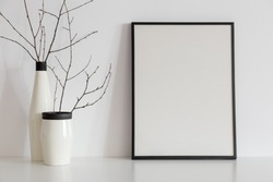 Twigs in a vase on book shelf or desk and blank photo frame. White colors.