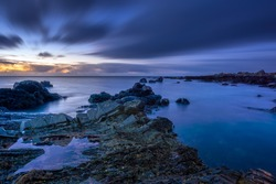 Twilight begins yielding to daylight at rocky coastline