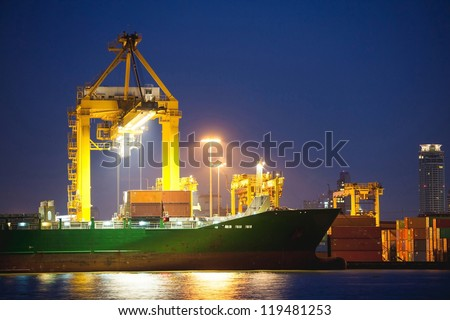 twilight Container Cargo freight ship with working crane bridge in shipyard at dusk for Logistic Import Export background