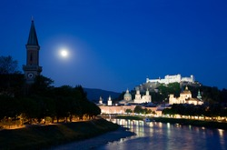Twilight in Salzburg, view on church, river banks and fortress on the hill