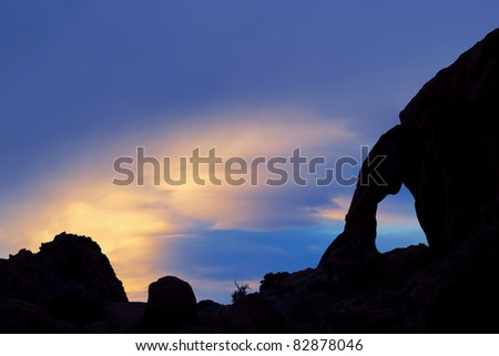 Twilight landscape of silhouetted arch, rock outcropping and lenticular clouds, Valley of Fire State Park, Nevada, USA #82878046