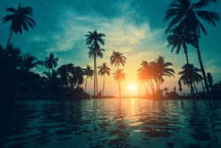 Twilight on a tropical beach with silhouettes of palm trees reflections in water.