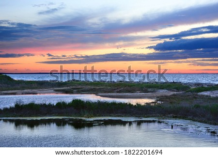 Twilight on Cape Cod Bay. View of colorful sky and clouds casting reflections on water at Corporation Beach in East Dennis, Massachusetts. Outlines of distant windmills visible along horizon.  Zdjęcia stock ©