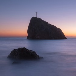 Twilight on the sea coast. Calm sea, picturesque rock with wood cross and beautiful cloudless sky. Peace, silence, meditation. Copy space on the colorful sunset sky.