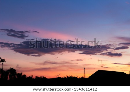 Twilight orange sky with dark cloud and Silhouette picture of home and jungle.