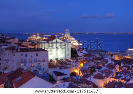 Twilight over Alfama quarter in Lisbon, Portugal) as seen from the Miradouro (Belvedere) de Santa Lucia with St-Stephen Church (Igreja de Santo Estevao) dominating the skyline.