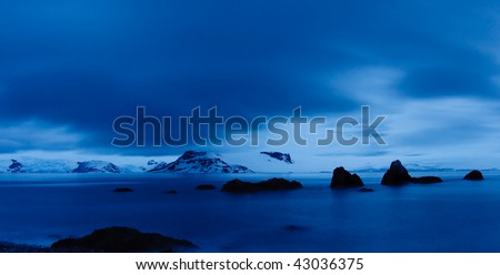 Twilight Scenery in Antarctica at Midnight. Dramatic Blue Light and Cloudscape.