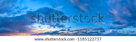 Twilight sunset with colorful clouds. Dramatic atmosphere created by the sunlight. Colorful gradient from blue to orange. Blue sky and clouds. High resolution panoramic sky. #1185122737