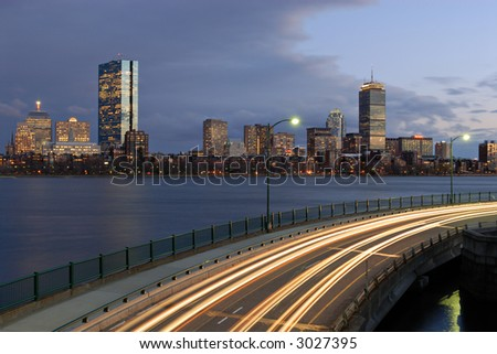 Twilight view of Boston skyline from Cambridge, Massachusetts. Memorial Drive and Charles river on foreground.