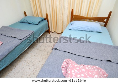 Twin beds in simple motel room. Suitable for concepts such as budget travel, tourism, vacation and holiday, and relaxation.
