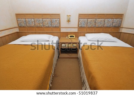 Twin beds neatly done up in a high class hotel room. Suitable for concepts such as travel, tourism, vacation and holiday.