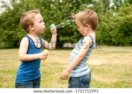 Twin blowing bubbles at brother in park