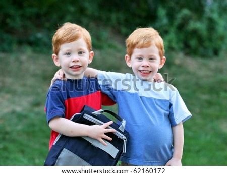stock photo : Twin boys with arms around eachother outside portrait