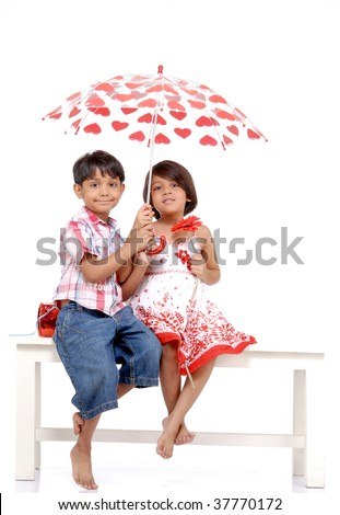 twin brother and sister covering each other in umbrella