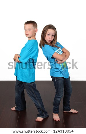 Twin brother and sister posing together in studio