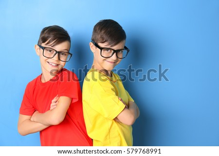 Twin brothers in glasses on blue background
