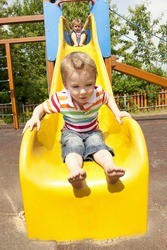 Twin brothers playing on yellow slide in playground