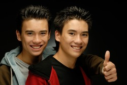 Twin brothers posing smiling gesturing OK