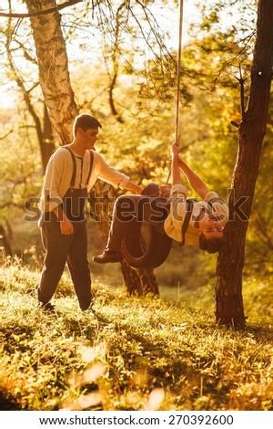 Twin brothers swinging on swing