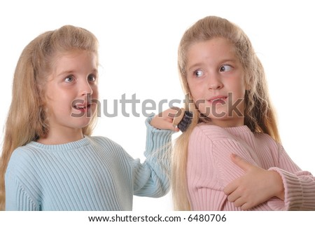 twin child brushing sisters hair