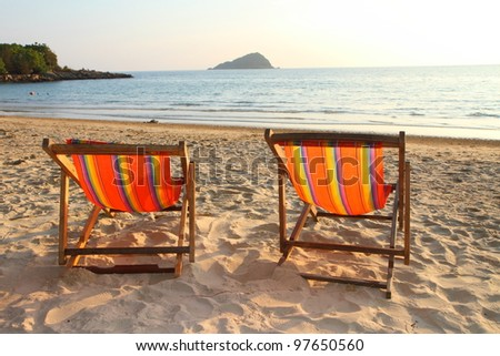 Twin deck chairs on the beach, at sunset