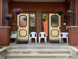Twin doors with plastic chairs on porch
