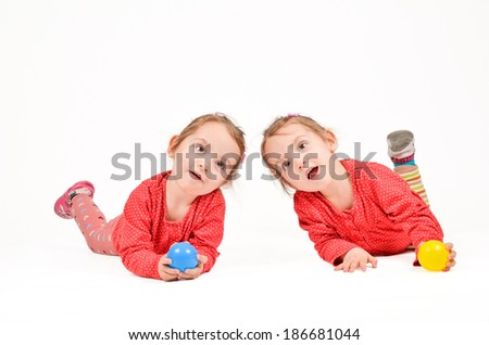 Twin Girls are playing with balls on white background