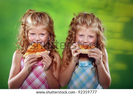 Twin girls eating pizza on the green background
