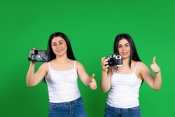 Twin girls posing with vintage camera and vintage video camera and showing class on green background.