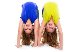 twin kid sisters playing as flexible contortionist happy on white background