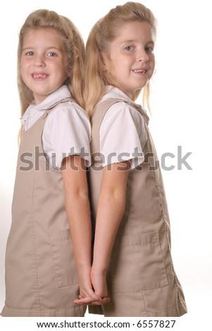 twin school girls vertical holding hands back