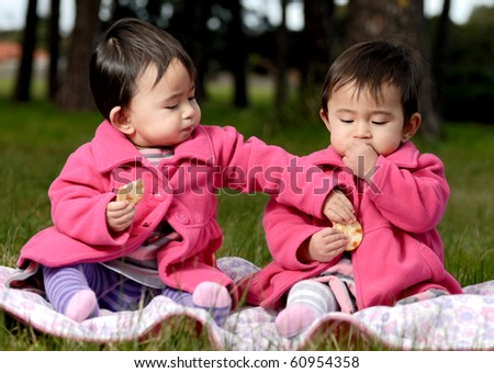stock photo : Twin sisters eating snack