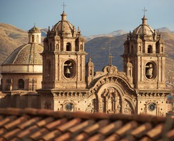 Twin towers and dome of the historic Iglesia de la Compania seen across the red rooftops of Cusco in Peru. The church dates back to 1571 and sits on top of an old Inca Palace.