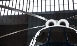 Twin-turbine helicopter is in the hangar. Rotor blades, turbines and cockpit. Selective focus.