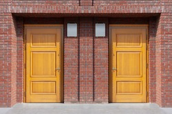 Twin wooden door, entrance to the house, red brick.
