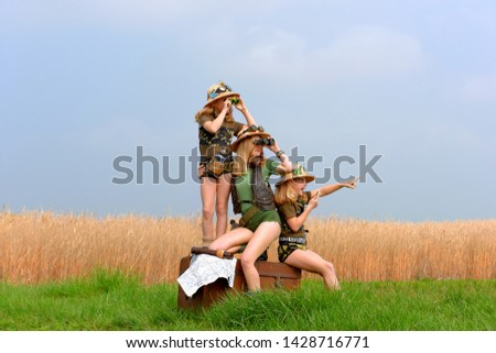 Twin young sisters and an adult girl dress up as explorers. They pose in the outdoors dressed with jungle hats and khaki safari clothes. #1428716771