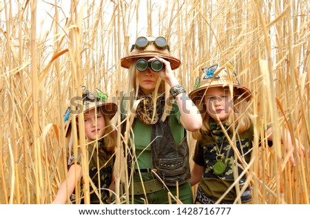 Twin young sisters and an adult girl dress up as explorers. They pose in the outdoors dressed with jungle hats and khaki safari clothes. #1428716777