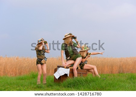 Twin young sisters and an adult girl dress up as explorers. They pose in the outdoors dressed with jungle hats and khaki safari clothes. #1428716780