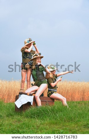 Twin young sisters and an adult girl dress up as explorers. They pose in the outdoors dressed with jungle hats and khaki safari clothes. #1428716783