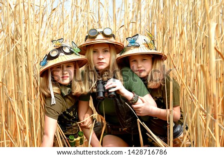 Twin young sisters and an adult girl dress up as explorers. They pose in the outdoors dressed with jungle hats and khaki safari clothes. #1428716786